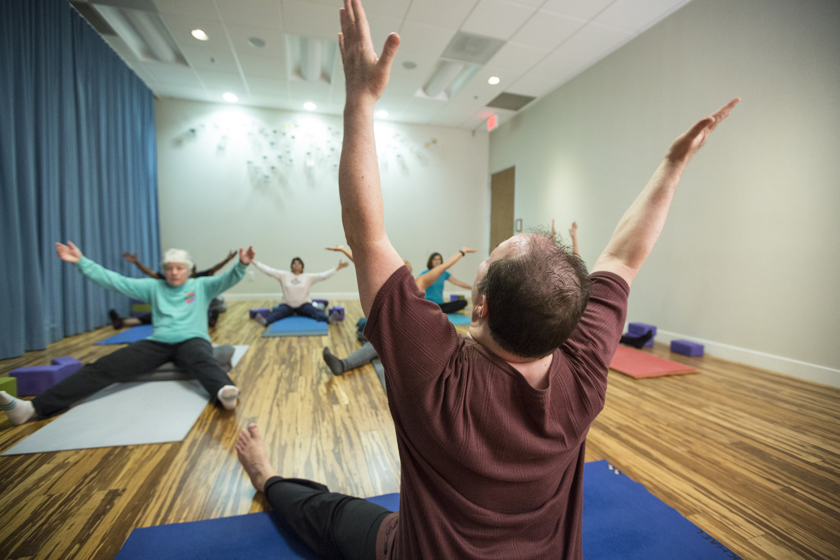 Male yoga instructor extends arms upward while seated in demonstration to yoga students.