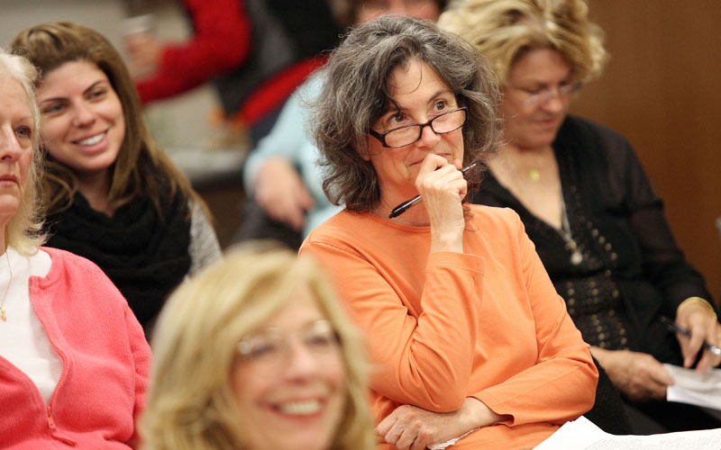 Group of women in audience attentively listening to presentation.