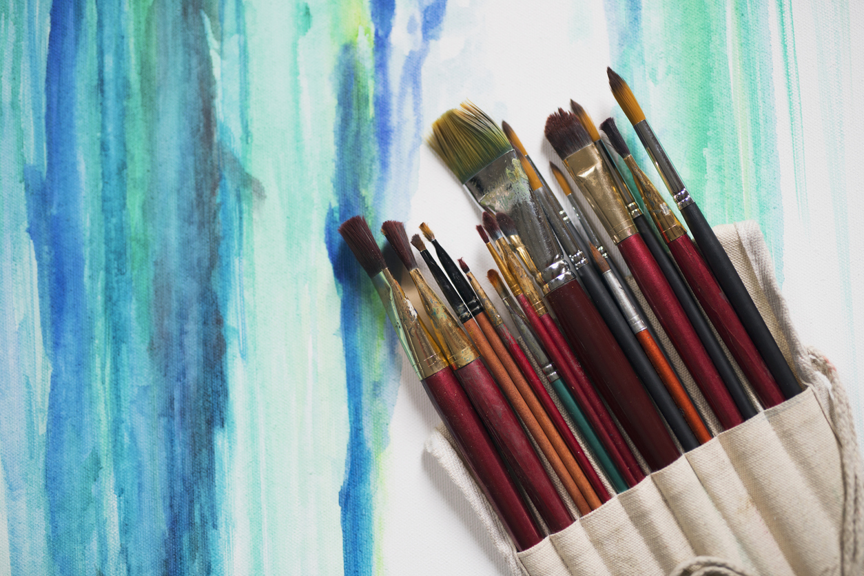 Paintbrushes over the watercolor painting.