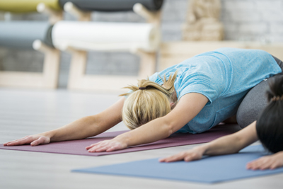 A Caucasian woman and an Asian woman are indoors in a fitness center. They are wearing casual athletic clothing. They are doing a stretching yoga pose on yoga mats.